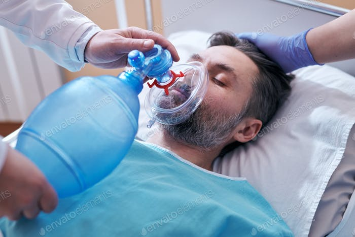 Placing bag valve mask on face of patient