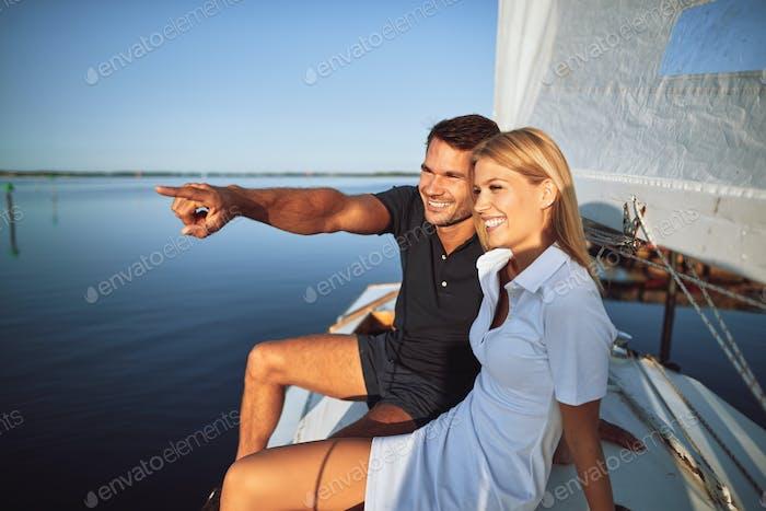 Lächelnd junges Paar genießen den Blick auf das Meer, während aus Segeln