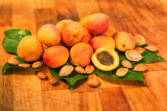 Fresh apricots, leaves and seeds on wooden surface