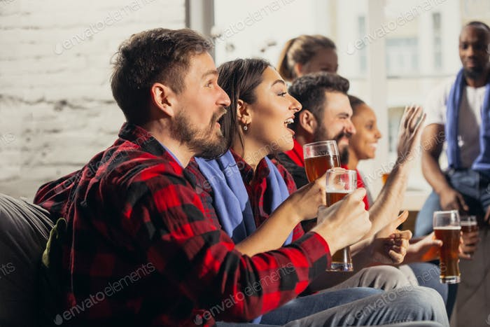 Excited group of people watching football, sport match at home
