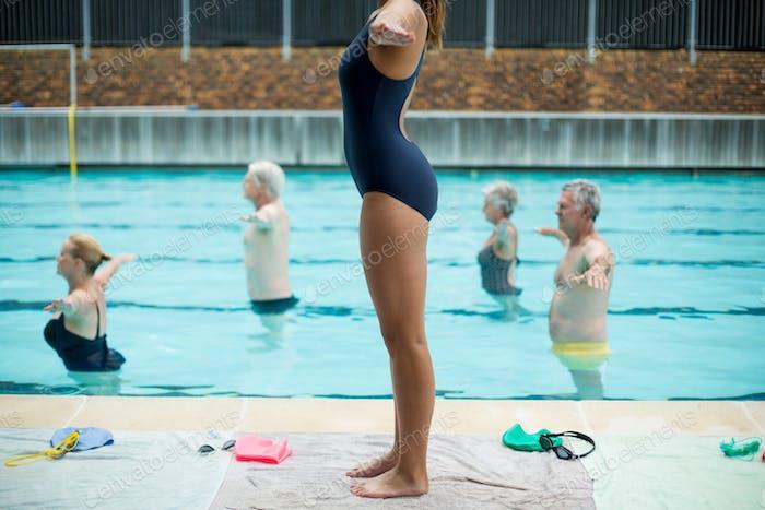 Female trainer preparing senior swimmers