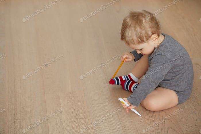 Little boy drawing lying on the floor in the living-room
