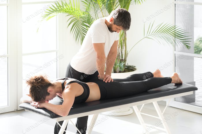 Osteopath doing sacrum mobility treatment