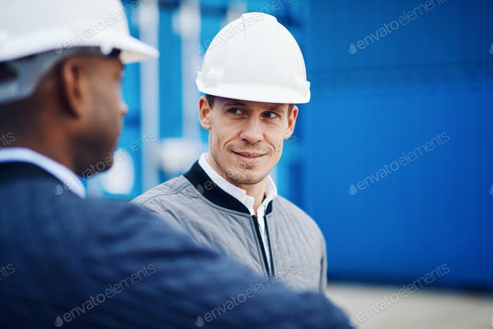 Port manager talking with an engineer in a shipping yard