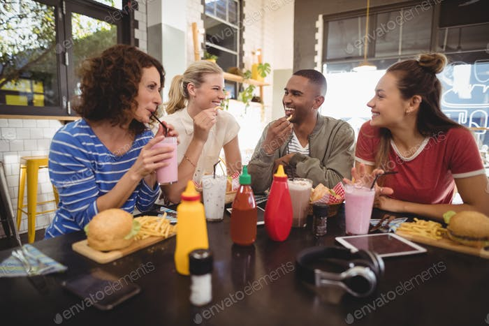 Young friends talking while sitting with food and drink at coffee shop
