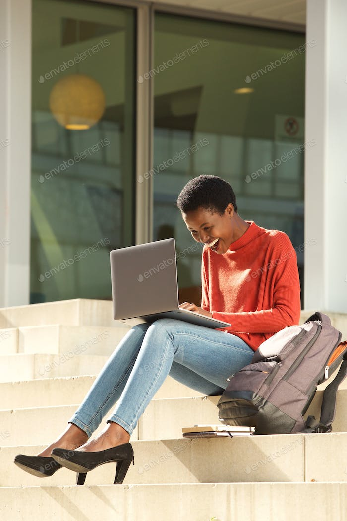happy african american female student working with laptop on college campus