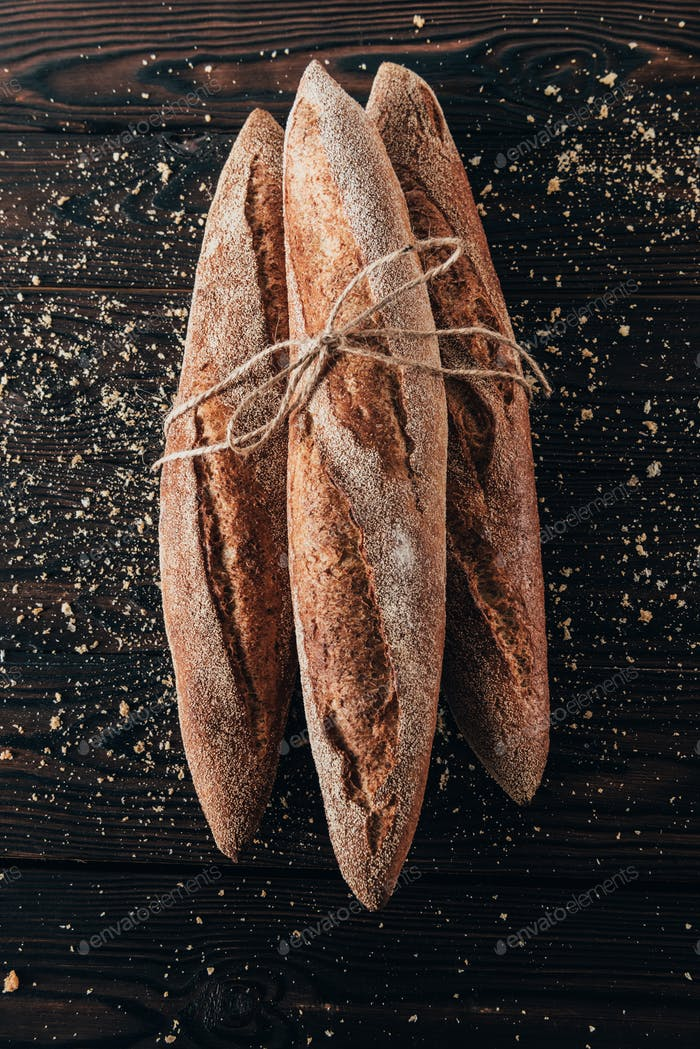 top view of french baguettes with rope on dark surface with flour