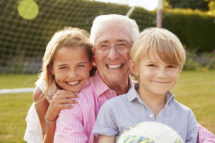 Senior man and grandchildren holding ball smiling to camera