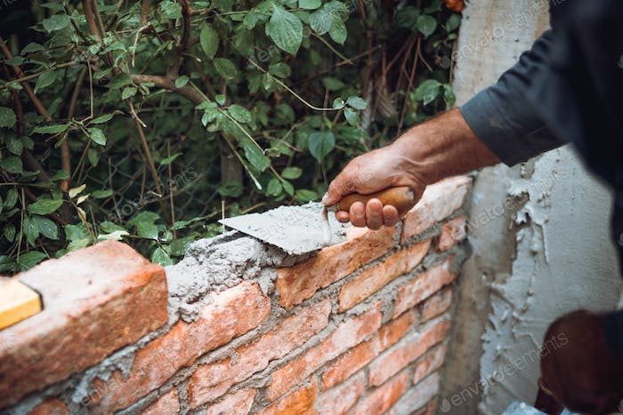 Close up of industrial worker, bricklayer installing bricks on exterior walls at construction site