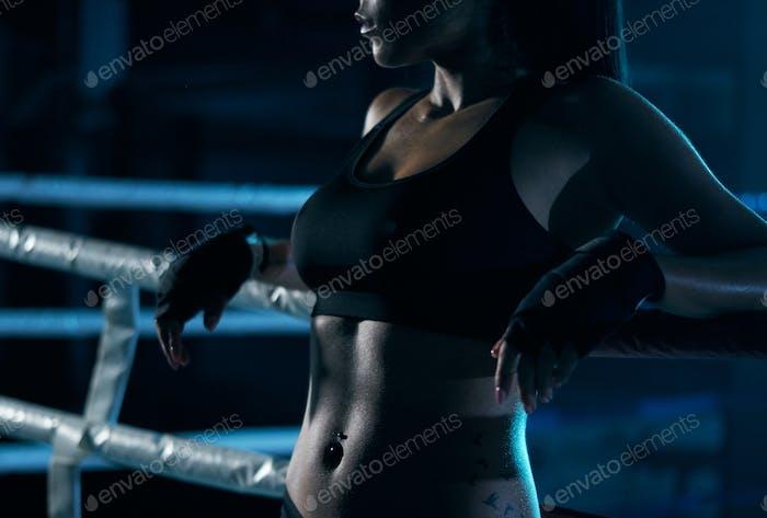 Weibliche Kämpferin posiert in der Nähe von Ring