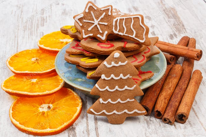 Decorated gingerbread with spices on old wooden background, christmas time