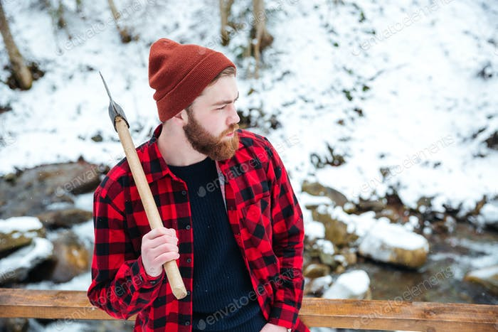 Pensive man in checkered shirt holding axe at winter forest
