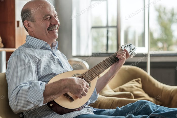 Senior hispanic man playing guitar singing and laughing.