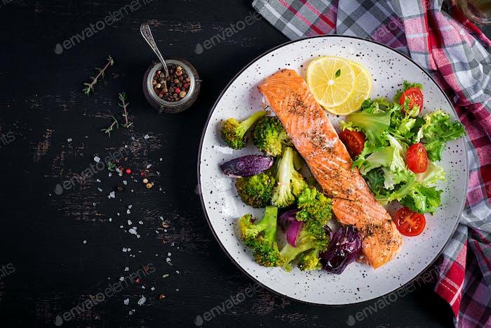 Gebackenes Lachsfilet mit Brokkoli, roten Zwiebeln und Zitrone. Draufsicht, Overhead