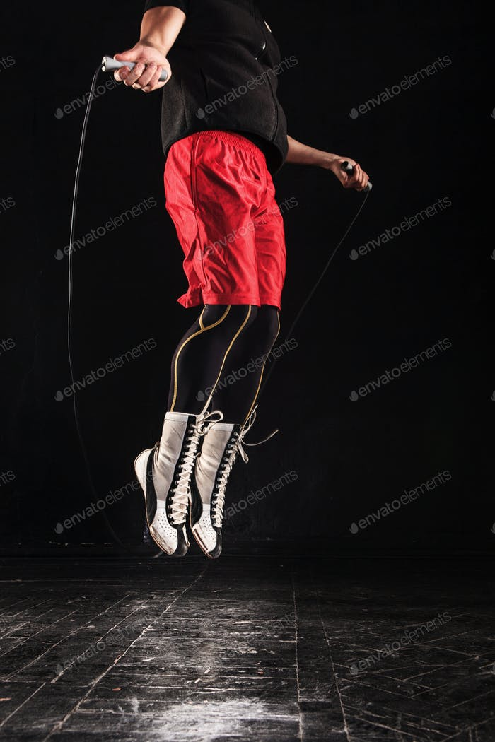 The legs of muscular man with skipping rope