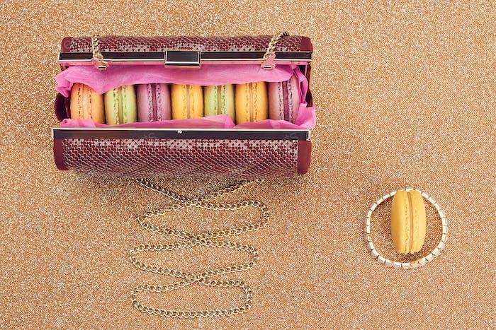 Macarons in shiny fashion handbag on gold.Vintage