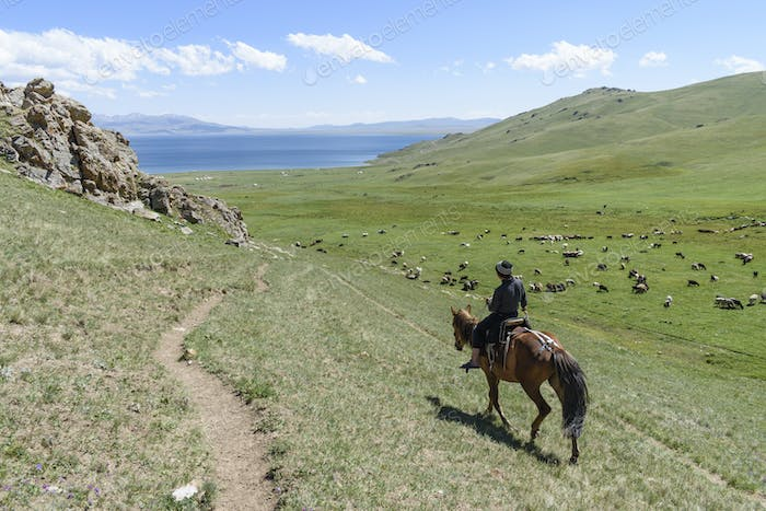 man on horseback riding through valley with lake in the distance, Song kul, Kyrgyzstan.