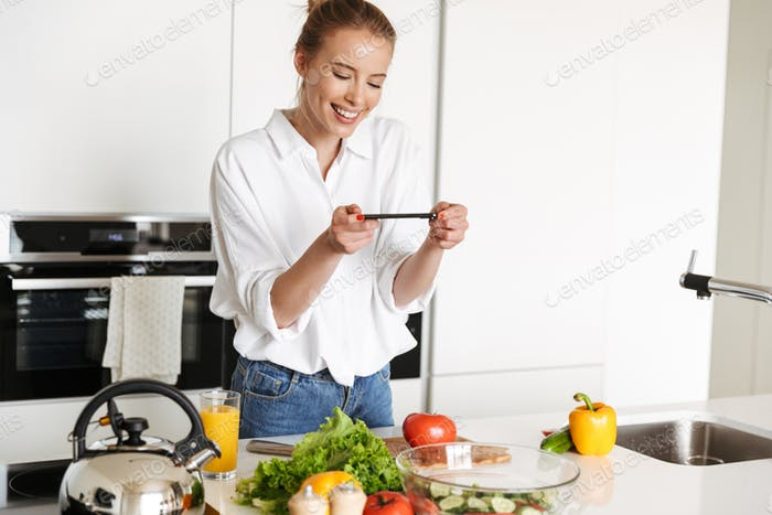 Young beautiful woman using mobile phone take a photo cooking.