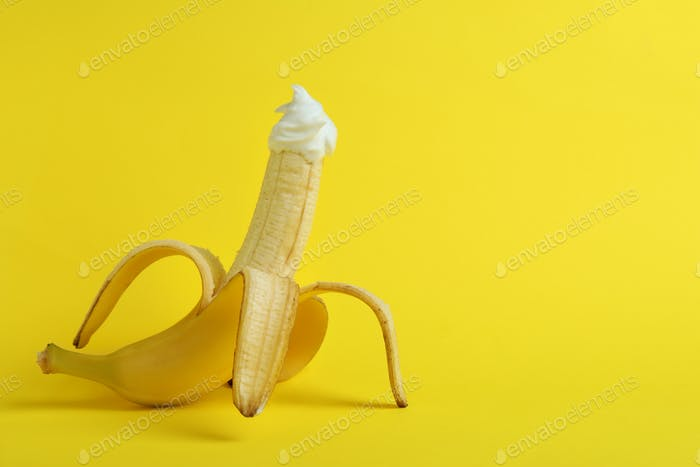 Banana with whipped cream on yellow background