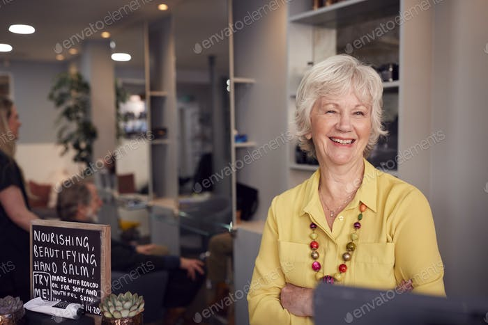 Senior Woman Arriving For Appointment To Have Hair Cut In Hairdressing Salon At Reception Desk