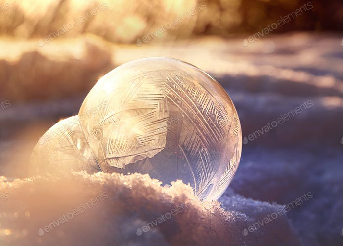 Frozen soap bubble ball against golden winter light