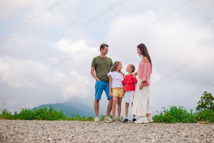 Beautiful happy family in mountains in the background of fog