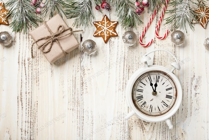 Christmas decoration and alarm clock on wooden background
