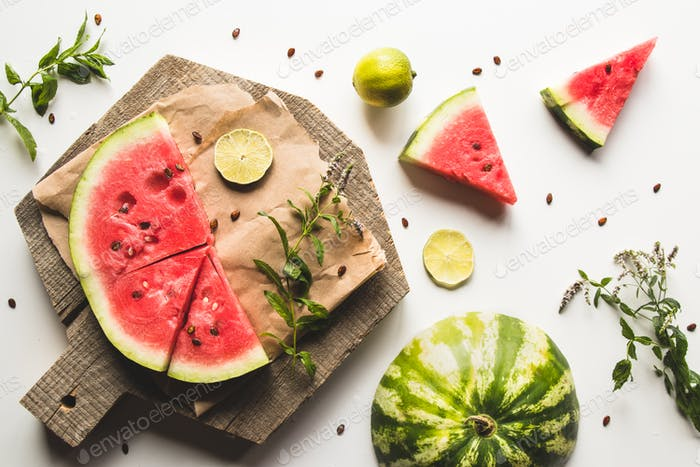 Wassermelone auf einem geschnittenen Brett mit Minze und Scheiben Limette. Essen