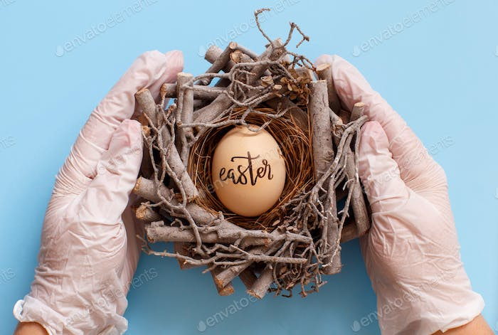 Hands in gloves keeping nest with egg with inscription EASTER