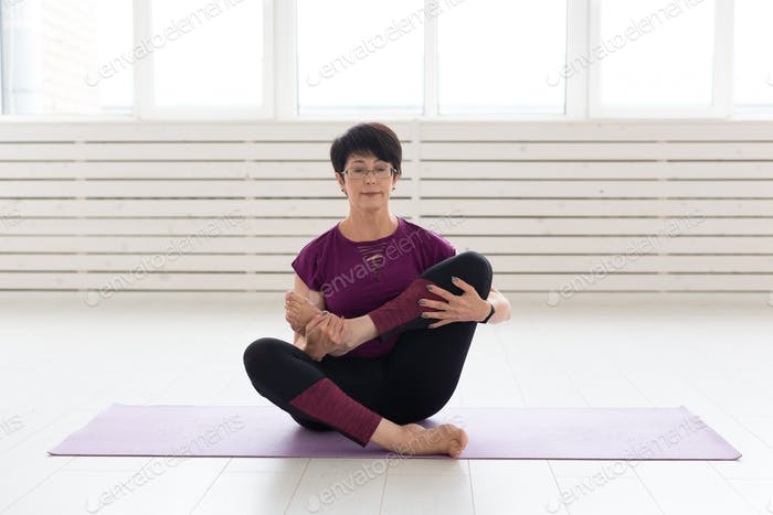 People, yoga, sport and healthcare concept - Attractive middle-aged woman stretching and sitting in