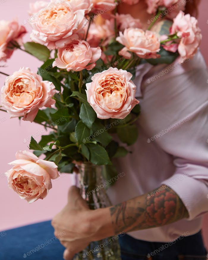 A large bouquet of fresh pink roses in a glass vase holds a girl statue on a pink background