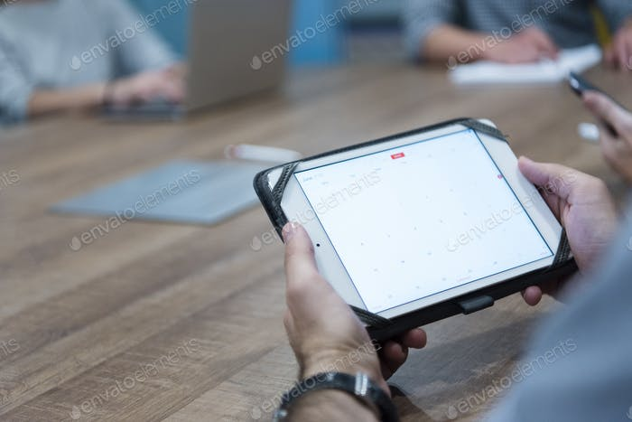 close up of businessman on meeting using tablet