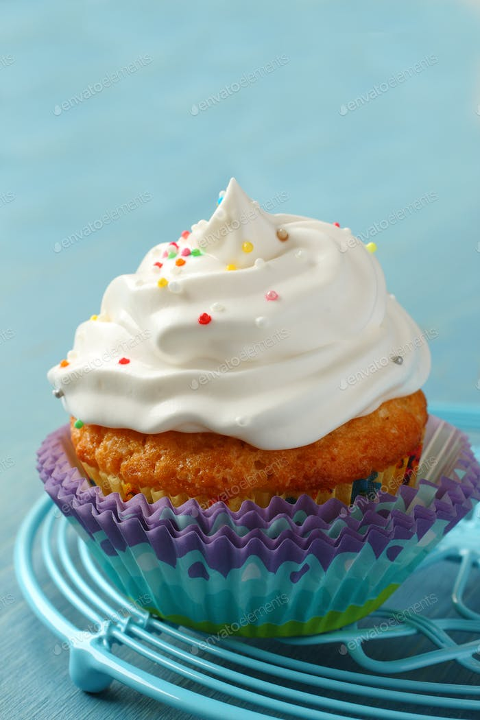 Cupcake with white cream icing and candy sprinkles