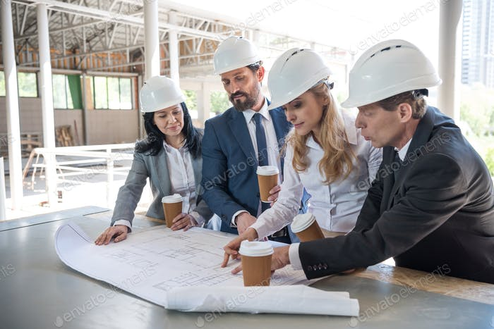 group of contractors in formal wear working with blueprints at construction area