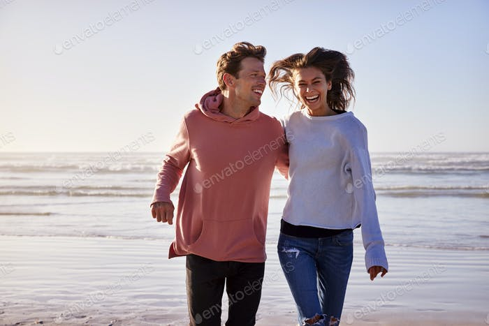 Couple Having Fun Running Along Winter Beach Together
