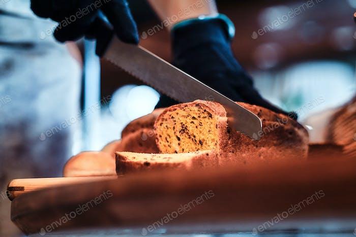 Trabajador de cocina está rebanando pan para el almuerzo