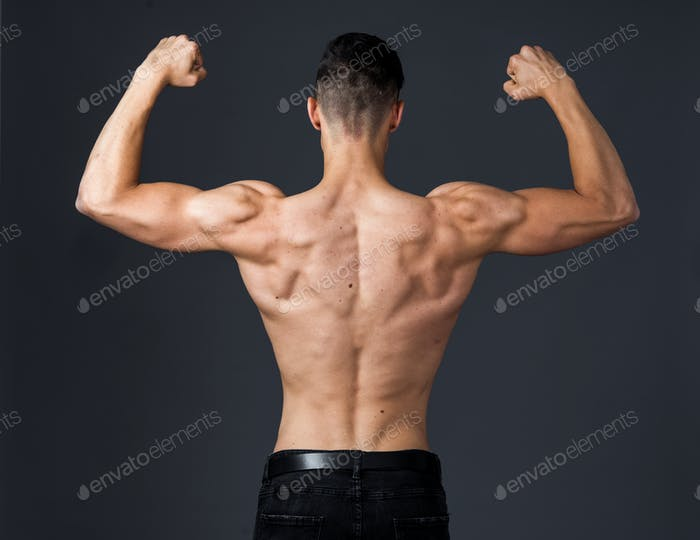 Muscular young man poses in studio with jeans and shirtless