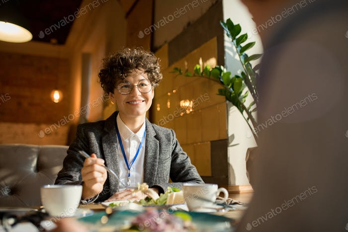 Happy businesswoman talking to colleague over lunch