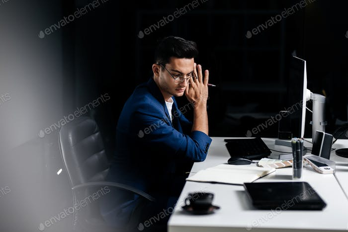 The architect in glasses dressed in a blue jacket sits at the desk in front of the computer and