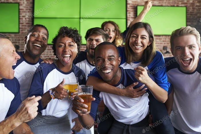 Porträt von Freunden beobachten Spiel in Sport Bar auf Bildschirmen