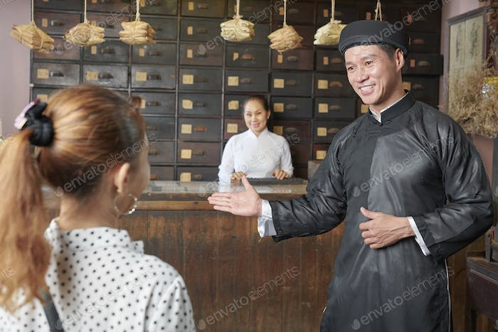 Apothecary worker talking to client