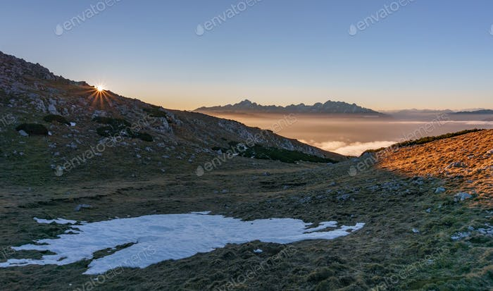 Beautiful mountain panorama at sunset with hikers and a dog