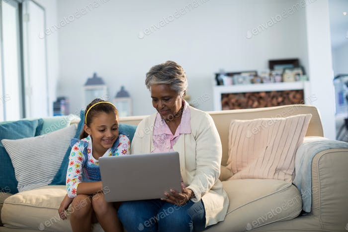 Grandmother and granddaughter using laptop in living room