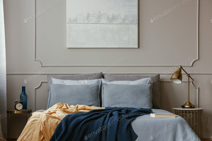 Pastel blue abstract painting above king size bed in elegant bedroom