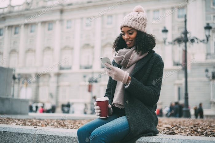 Young black woman on the mobile phone near the royal palace in winter