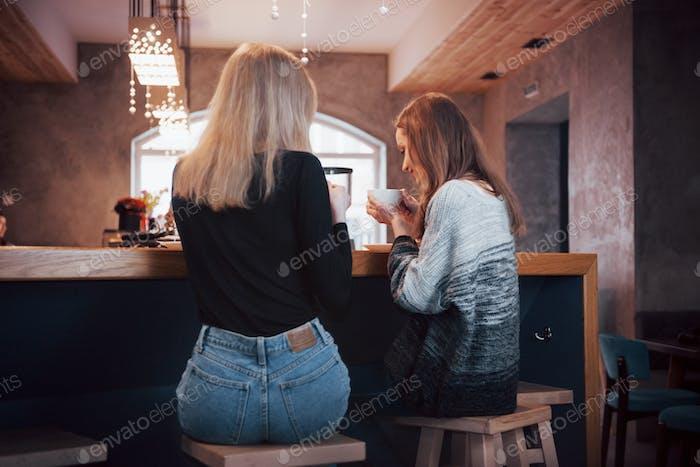 Getöntes Bild von besten Freunden, die eine Verabredung im Café oder Restaurant haben. Schöne Mädchen sprechen oder