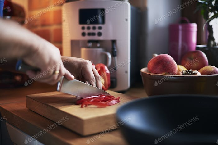 Man cutting red pepper in the kitchen