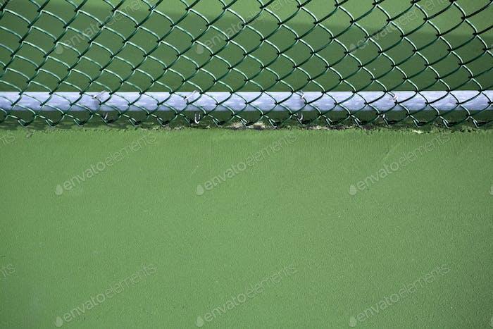 Kettengliederzaun und grüner Tennisplatz