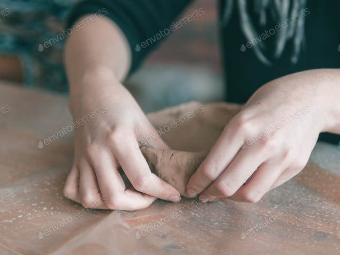 Ceramist hands make a plate of clay
