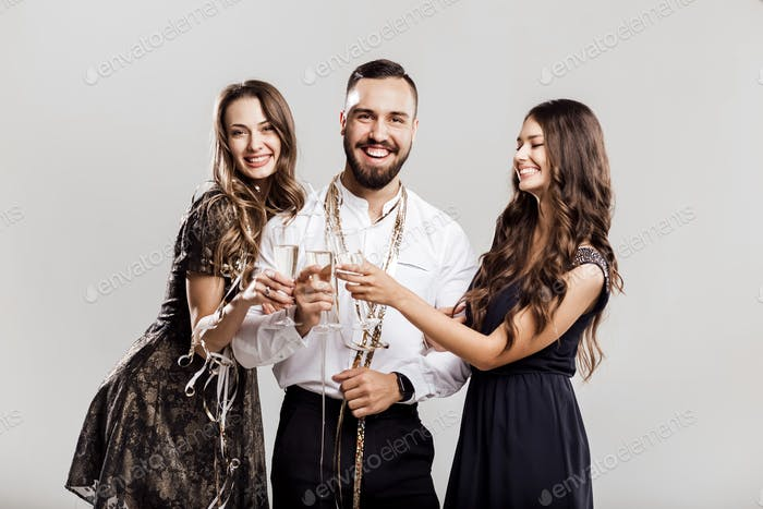 Party time. Two beautiful girls dressed in elegant dresses and handsome man in the white shirt hold